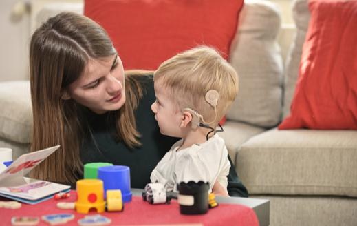 Un niño con implantes cocleares jugando con una mujer joven