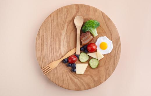 plato de madera con alimentos y cubiertos como un reloj
