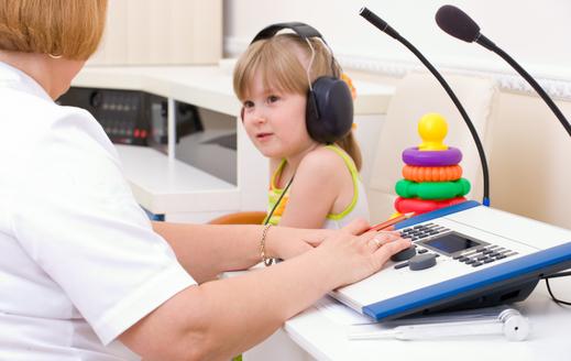 Una enfermera hace un diagnóstico de audición de una niña con cascos grandes